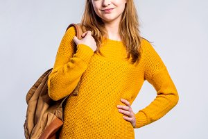 Girl in jeans and sweater, young woman, studio shot