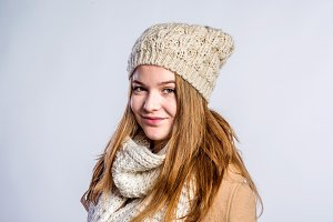 Girl in brown coat, scarf and hat, studio shot
