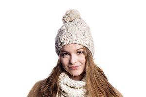 Girl in winter coat, scarf and hat, studio shot, isolated.