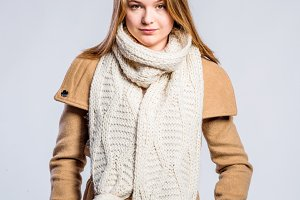 Girl in brown coat and knitted scarf, studio shot