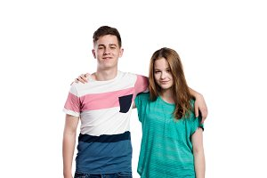 Teenage boy and girl, arms around each other, isolated.