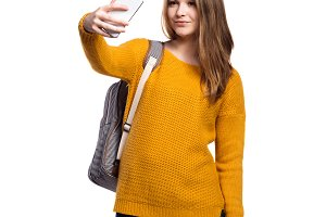 Girl in yellow sweater, holding smartphone, taking selfie, isola