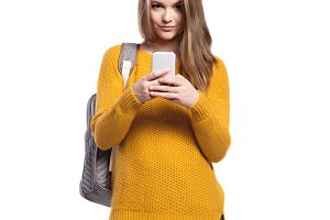 Girl in jeans and sweater, holding smartphone, texting, isolated