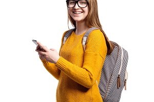 Girl in yellow sweater and eyeglasses holding smartphone, isolat