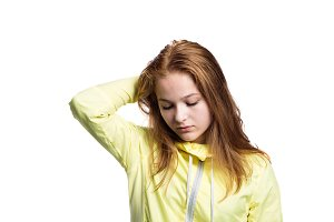 Teenage girl in yellow running jacket. Studio shot, isolated.