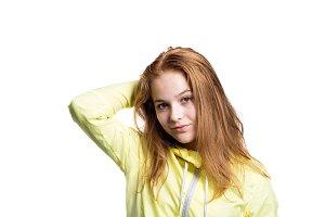 Teenage girl in yellow running jacket. Studio shot, isolated.