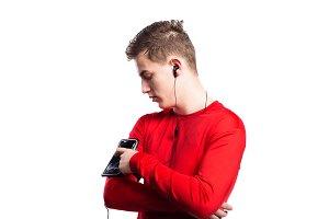 Teenage boy with smartphone and earphones. Studio shot, isolated
