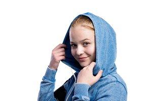 Teenage girl in blue sweatshirt. Studio shot, isolated.