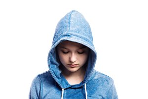 Teenage girl in blue sweatshirt. Studio shot, isolated.