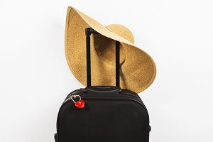Black suitcase, red lock and hat