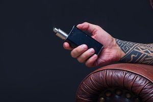 Hand close up. Vaper. The man with tattoos sits on a leather sofa smoke an electronic cigarette on the dark background