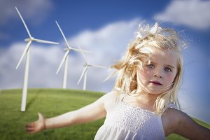 Little Girl Playing by Wind Turbines