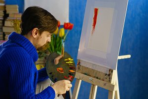 Artist paints with oil paints