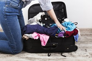 Young girl casually packs suitcase