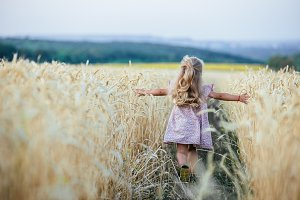 happy running girl on a wheat field
