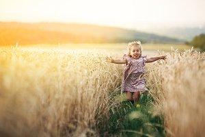 happy running girl on a wheat field
