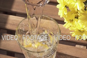 Water in a glass with bubbles and lemon slow motion