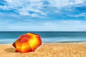 Orange umbrella on golden sand beach