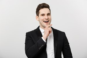 Business Concept: Smiling thoughtful handsome man standing on white isolated background and touching his chin with hand