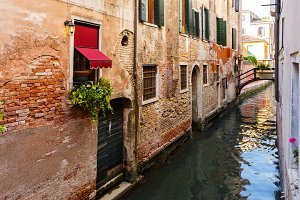 Typical tiny bridge on Venice canal. Flowers on windows with Venetian shutters
