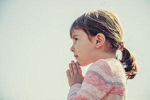 The child prays to God.