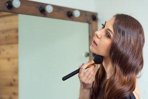 Young woman apply makeup.