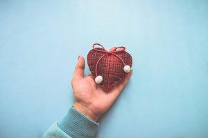 Woolen heart in hand.