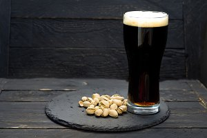 A glass of dark beer and pistachios. A tray of slate.