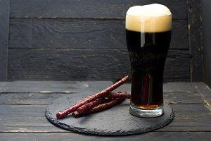 Dark beer with foam. Fresh dark beer and spicy sausages.