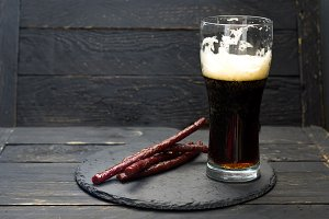 A half-empty glass of beer. Dark beer and sausages.