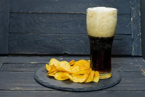 A glass of dark beer and chips. Serving on a slate tray.