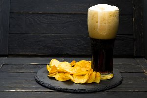 A glass of dark beer and chips. Beer Foam.