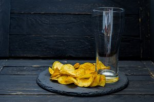 Empty beer glass and chips. A glass for beer.