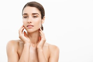 Beauty Skin Care Concept - Beautiful Caucasian Woman Face Portrait. Beautiful beauty young female model girl touching her face skin cheeks hands fingers. Fashion Beauty Model isolated on white