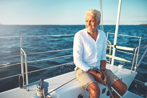Smiling mature man sailing his yacht on a sunny day