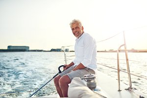 Smiling mature man sailing his boat along the coast