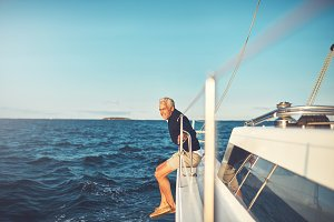 Mature man admiring the sea view from his sailboat