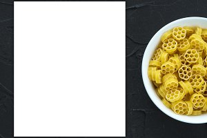 Macaroni ruote Pasta in a white bowl on a black textured background from the side. Close-up with the top. White space for text and ideas.