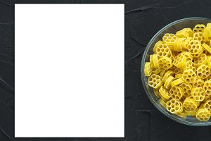 Macaroni ruote Pasta in a glass cup on a black textured background from the side. Close-up with the top. White space for text and ideas.