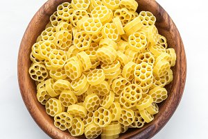 Macaroni ruote pasta in wooden bowl on white isolated background, in the center close-up with top.