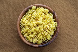 Macaroni ruote pasta in a wooden bowl on a brown rustic texture background, in the center close-up from the top.