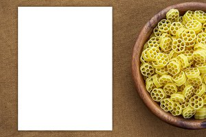 Macaroni ruote pasta in a wooden bowl on a brown rustic background texture with a side. Close-up with the top. White space for text and ideas.