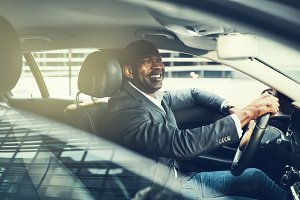 Smiling African businessman driving through city traffic