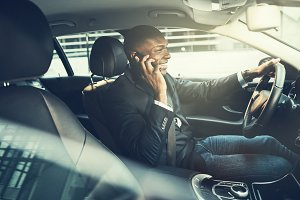 Smiling African businessman talking on a phone in his car