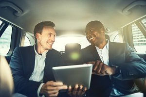 Smiling colleagues working online together in a car backseat