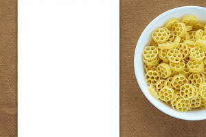 Macaroni ruote pasta in a white bowl on a brown rustic background texture with a side. Close-up with the top. White space for text and ideas.
