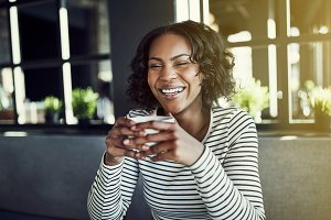 Young African woman laughing and enjoying a cafe coffee