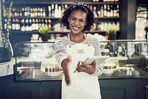 Smiling African entrepreneur offering a handshake in her cafe