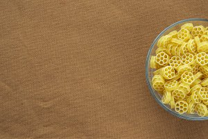 Macaroni ruote Pasta in a glass cup on a brown suburban background texture with a side. Close-up with the top. Free space for text.