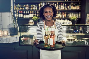 Smiling young African waitress holding a tray of drinks